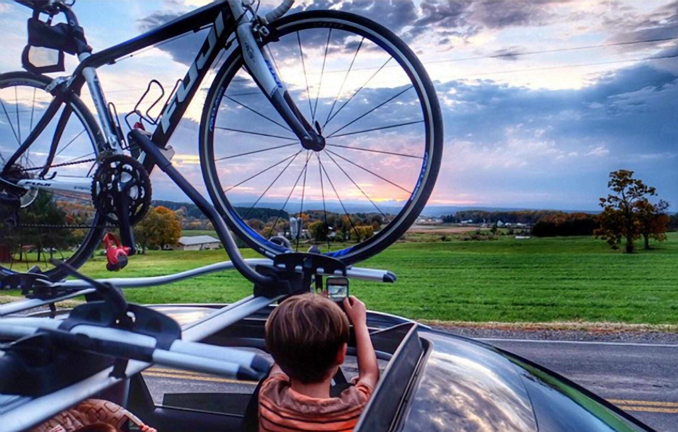 bicycle on top of bike with boy looking out over Ithaca landscape