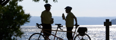 two people taking a water break next to their tandem bike and Cayuga Lake