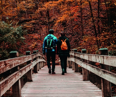 two hikers cross wooden bridge in Ithaca, NY